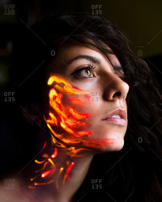 Young woman with orange luminous paint on face looking away.