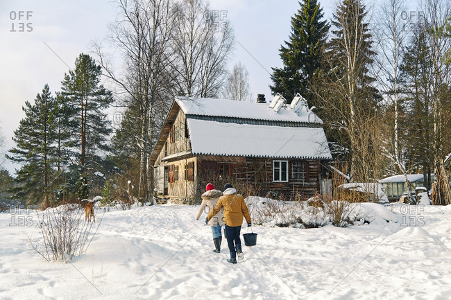 Two persons carrying water to the farmhouse in winter
