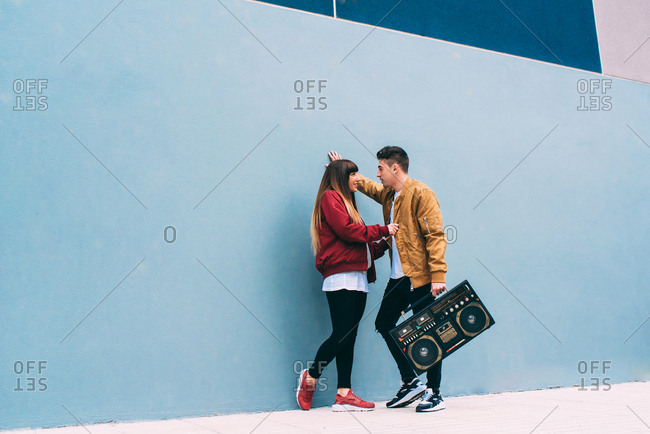 Young happy couple dancing on the street with a vintage radio cassette stereo