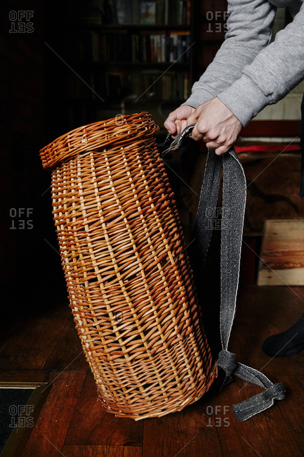 Male hands holding handmade wicker basket for carrying apples