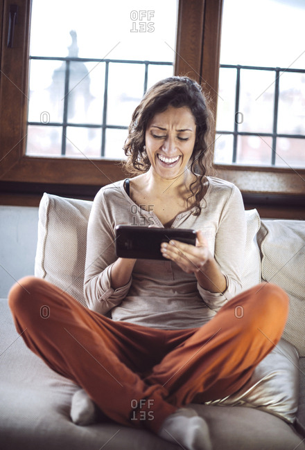 A young woman holding a Tablet PC on the sofa