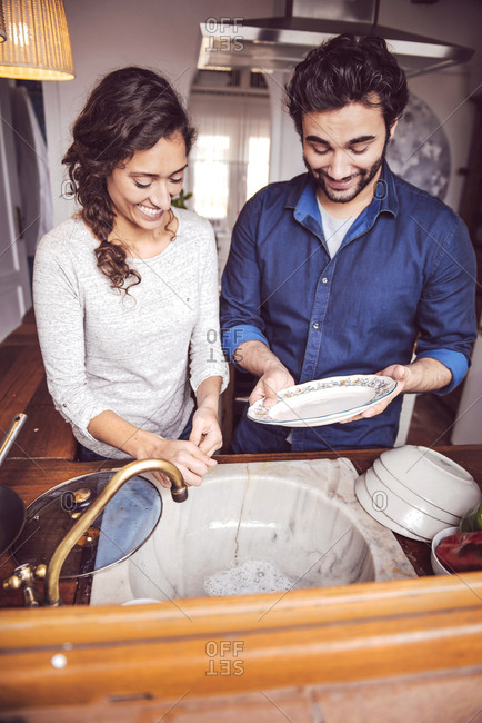 Young couple washing dishes in the kitchen