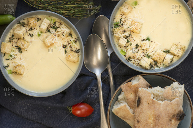 Top view of two bowls with appetizing creamy soup and bread with spoons.