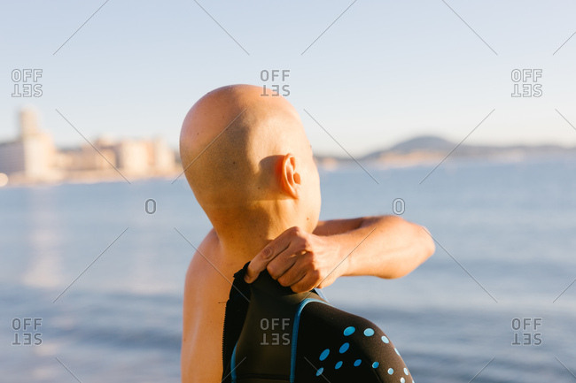 Bald anonymous man standing on shoreline of ocean and putting on wetsuit.