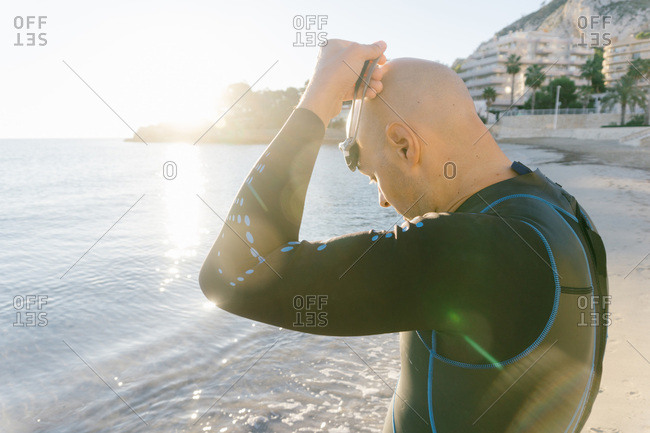 Man in wetsuit putting on glasses before swimming in cold ocean water.