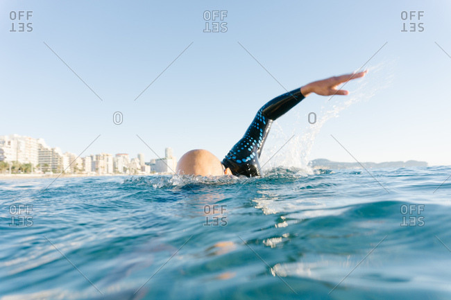 Man in wetsuit swimming in ocean