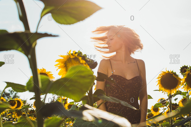 Pretty young woman in sunflowers