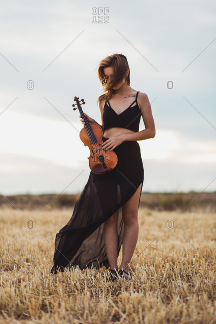 Young Pretty Woman In Black Dress Standing With Violin On Dry Field