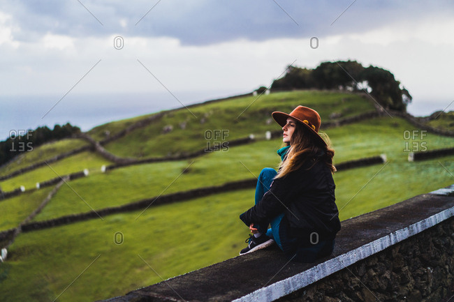 Young dreamy woman sitting on fence at green field on hill.
