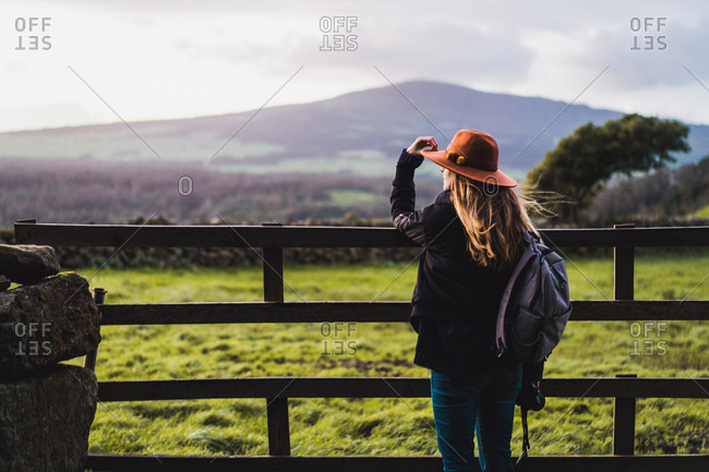 Dreamy woman standing at fence on field