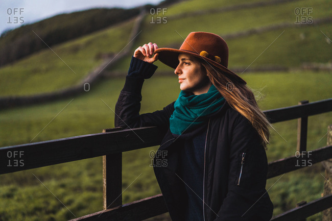 Side view of dreamy woman in hat standing at fence and looking away on green field.