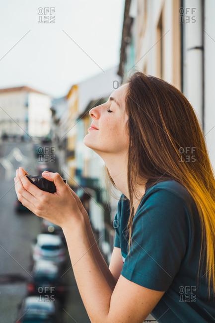 Charming brunette on balcony in cityscape