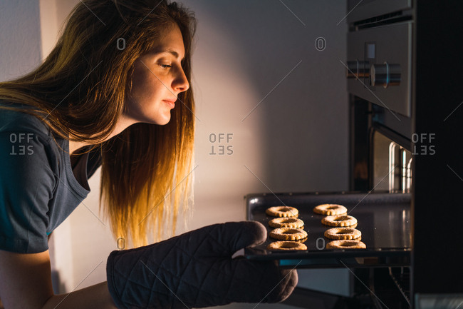Side view of girl checking progress of making delicious cookies on sheet pan in oven.