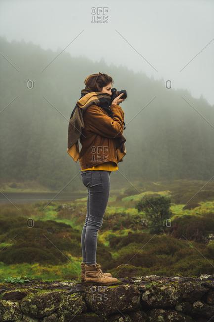 Woman taking photo in misty woods