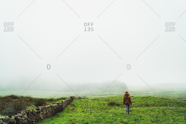 Content woman in green foggy fields