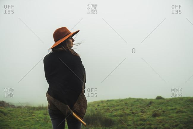 Woman in green foggy fields