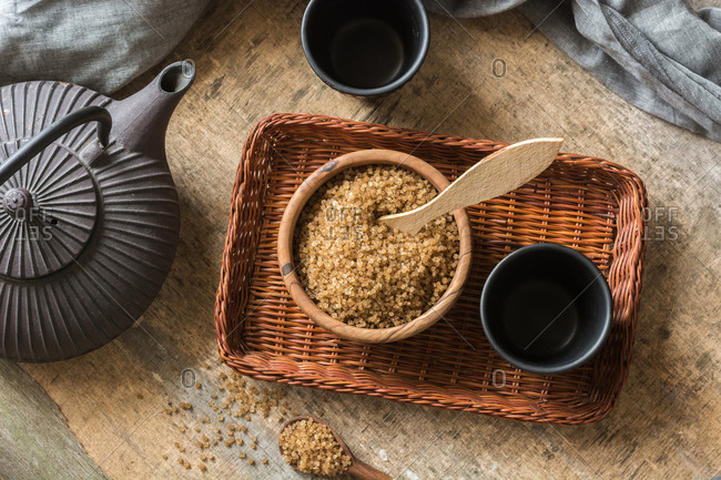 Wooden Bowl full of sugar cane brown, accompanied by a teapot. Ideal ingredient for health