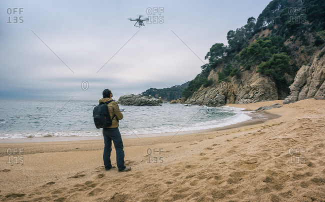 Man on a single beach testing its drone and recording videos from the air
