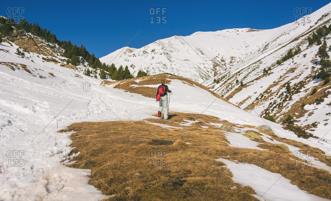 female hiker going up a mountain with snow on a sunny day in the Pyrenees