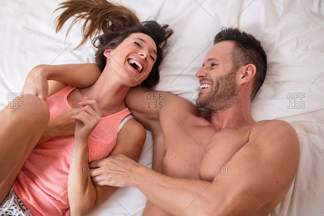 From above young laughing couple lying and relaxing on bed.