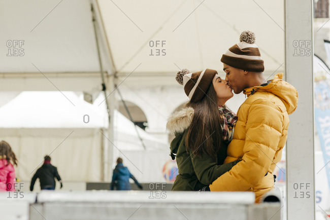 Cheerful couple embraced on rink