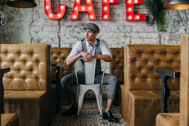 Stylish man in cap in cafe