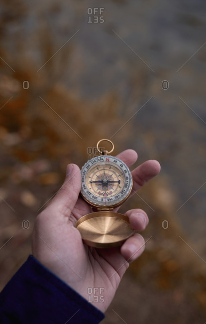Hand with compass in nature