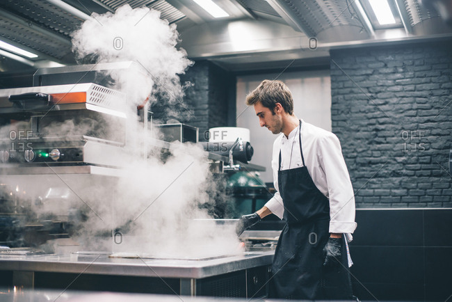 Young cook standing on kitchen of restaurant and cooking with smoke.