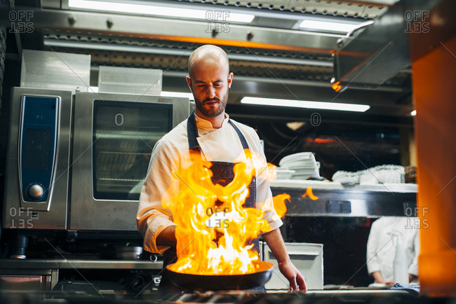Adult chef standing in restaurant and making flambe on frying pan.