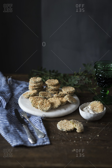 Arranged zucchini slices in bread crumbs served with bowl of dip sauce on table.