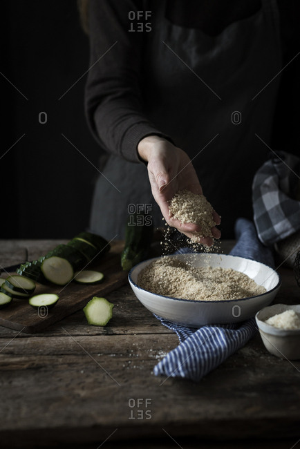 Crop hand throwing breadcrumbs