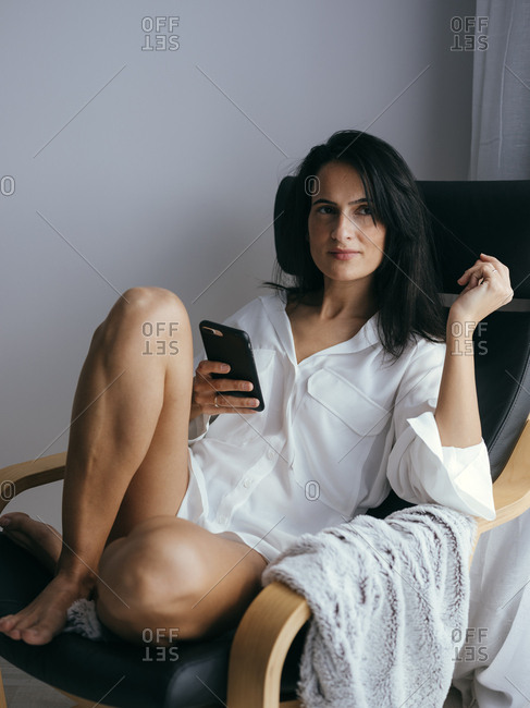Woman using phone in chair