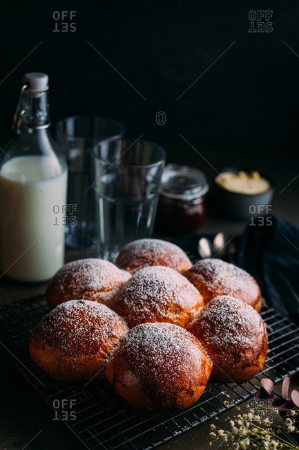Delicious brioche with icing sugar, with milk, butter and jam at background
