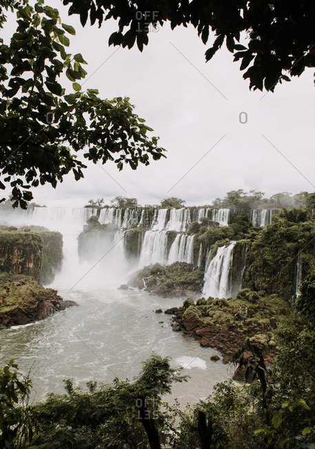 View to river and waterfall in green forest in cloudy day.