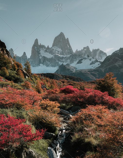 View to colorful autumn forest and mountains covered with snow.