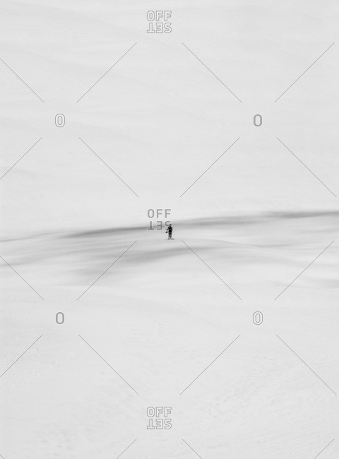 Black and white minimalistic shot of unrecognizable person standing in the sand.