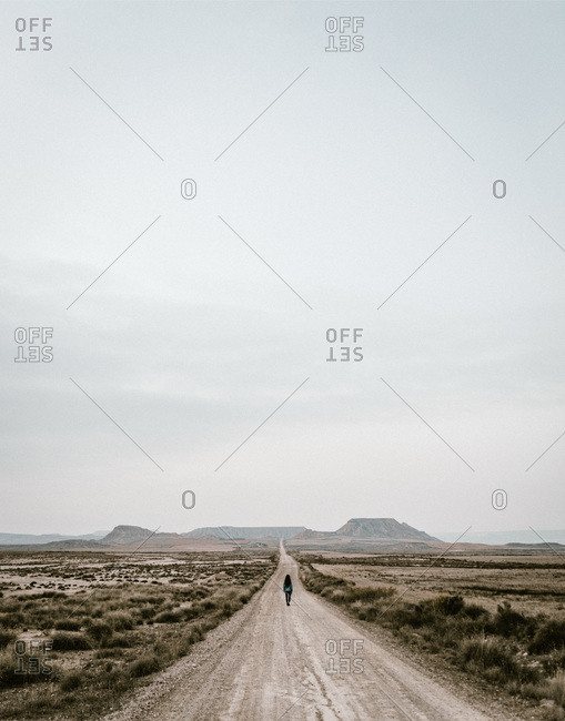 Unrecognizable person walking on rural road in field with dry grass.