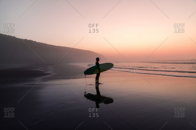 Unrecognizable man with surfboard standing on wet sandy beach at the ocean.