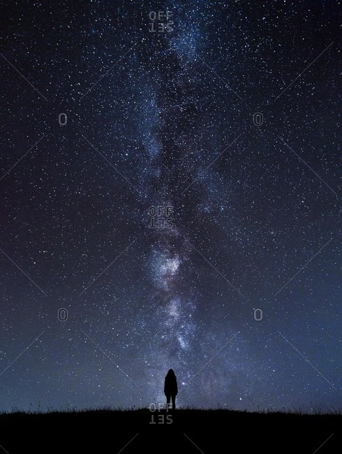 Silhouette of unrecognizable tourist standing under cosmic sky at night.
