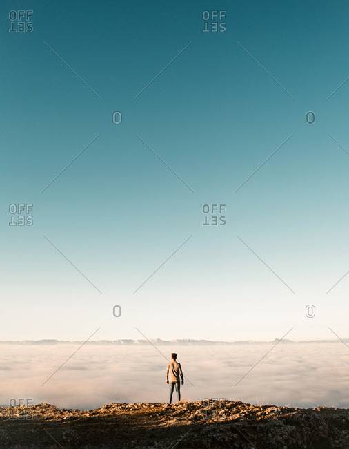 Back view of tourist standing at cliff edge over the clouds.