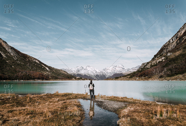 Back view of hiker with backpack standing at lake in mountains.