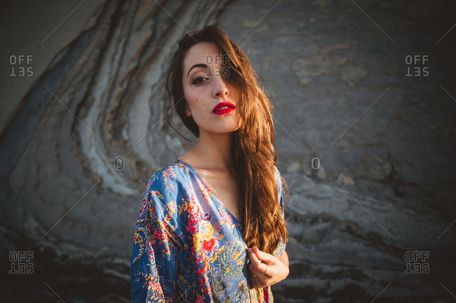 Portrait of alluring model with red lips looking at camera in sunlight on background of cliff.