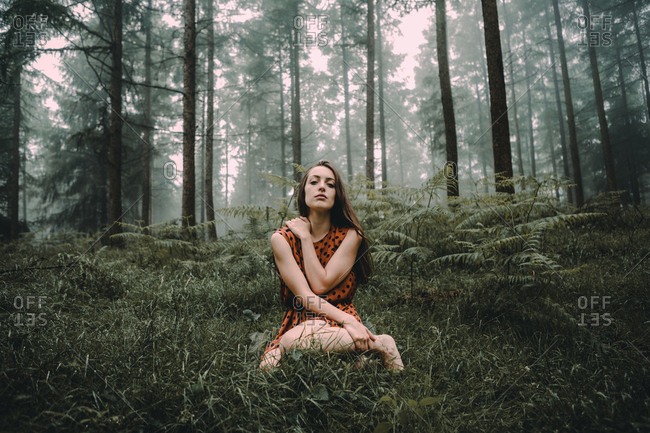 Model in dress standing in spooky woods