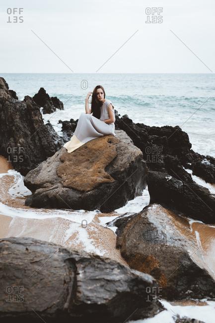 Tender model in dress on coast rock