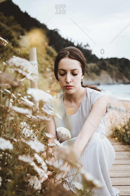 Tender woman with flower on coast