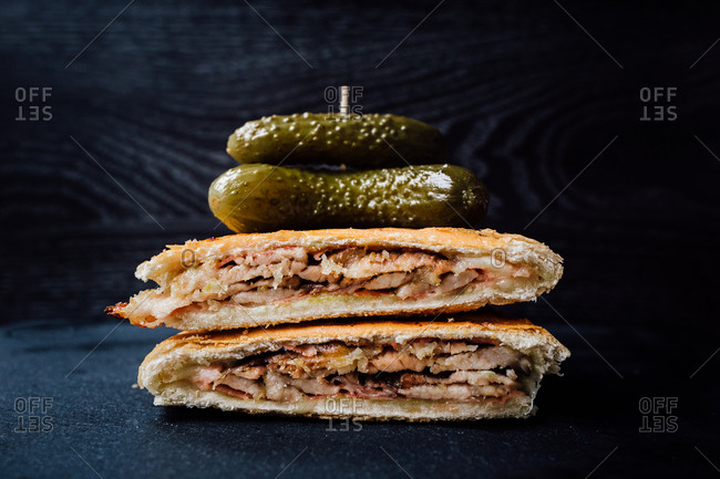 Medianoche sandwich served with whole sweet pickles