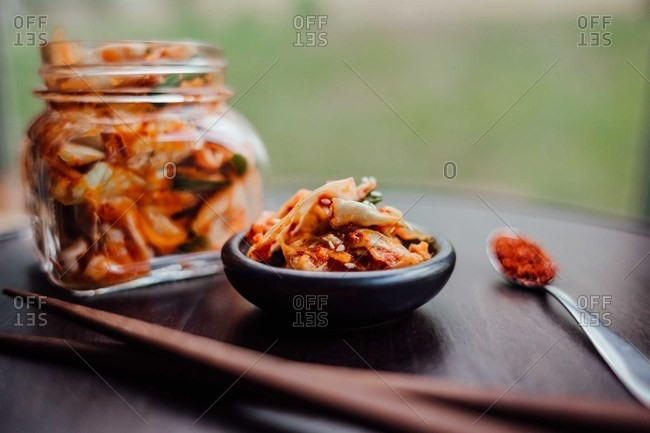 Glass jar and bowl of homemade kimchi served with chopsticks