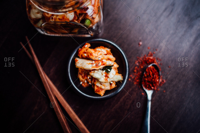 Bowl of homemade kimchi served with chopsticks and a spoonful of chili pepper flakes