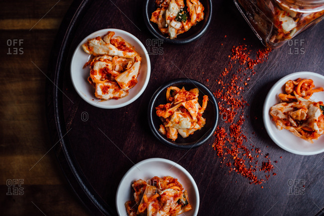 Bowls of kimchi served with red chili pepper flakes