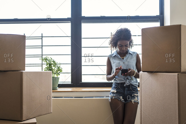 Woman using smart phone while leaning on window sill by cardboard boxes at new home
